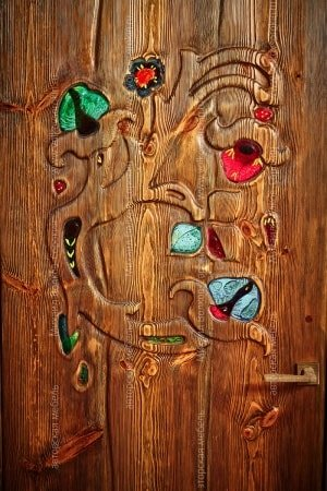 Fragment of a door with a carving and stained-glass windows